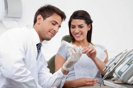 Happy young male dentist prescribing tooth paste to female patient in clinic Stock Photo - 15316614