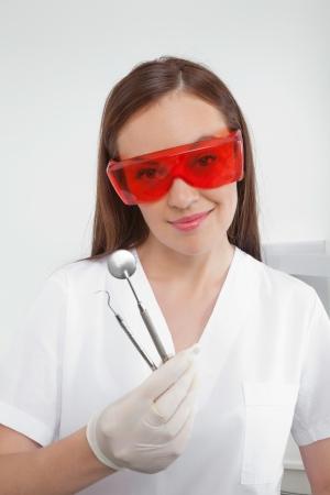 gloves nurse: Portrait of dental nurse wearing eyewear while holding angled mirror and carver