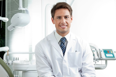 Retrato de hombre feliz dentista llevaba bata de laboratorio mientras está sentado en la clínica