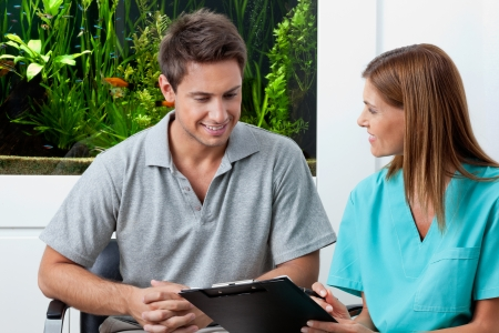 nurse and patient: Female dentist with clipboard explaining something to man in clinic