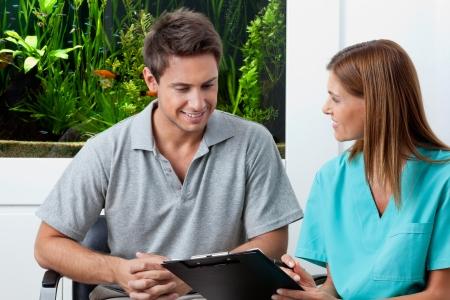 enfermera con paciente: Mujer dentista con portapapeles explicar algo al hombre en clínica