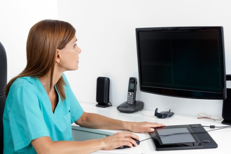Female dentist using computer at office desk photo
