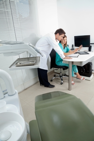 Doctor and female assistant in discussion with dentist chair in foreground photo