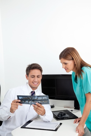 Young dentist and female assistant analyzing X-ray report at office desk Stock Photo - 15316581