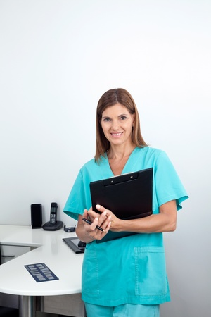 Portrait of a happy female dentist holding clipboard in dental clinic Stock Photo - 15316600