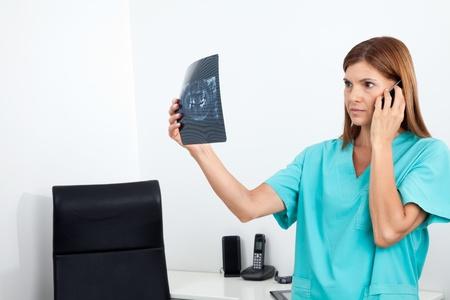 comunicacion oral: Dentista mujer seria mirando de rayos X durante el uso de teléfono celular informe en la clínica