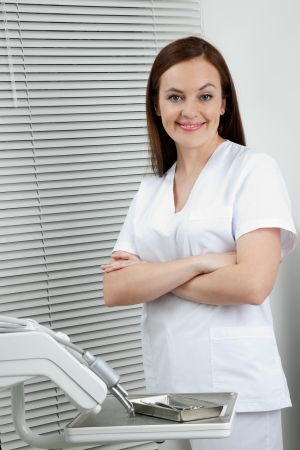 Portrait of happy confident female dentist standing with arms crossed in clinic photo