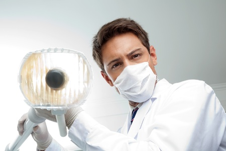 Portrait of young male dentist wearing surgical mask while holding dental lamp photo