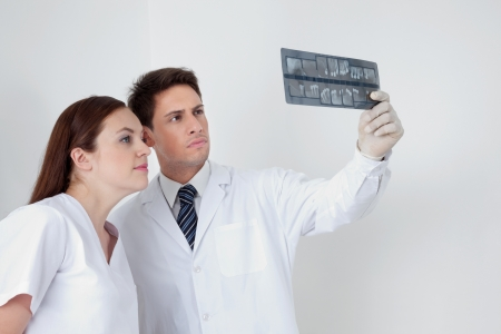 hygienist: Dentist with dental nurse analyzing patient s X-ray report in clinic Stock Photo