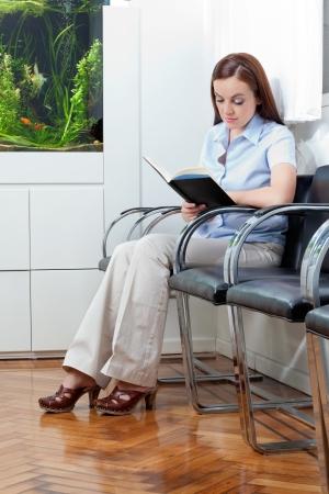 mujer leyendo libro: Longitud total de un libro de lectura de la mujer joven en la sala de espera m�dico s