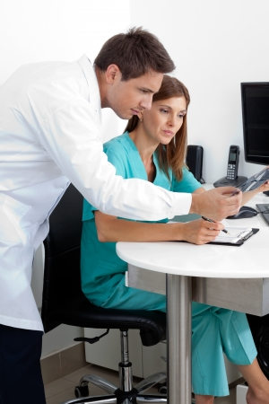 Male dentist and assistant checking X-ray at dental clinic Stock Photo - 15316609