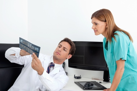 Male dentist and female assistant analyzing X-ray report at office desk Stock Photo - 15316577