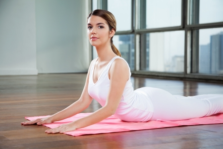 Portrait of a beautiful young woman in a cobra pose on mat Stock Photo - 15316621