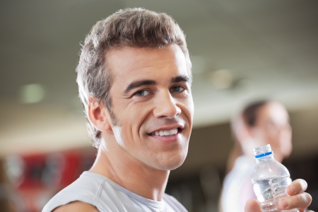 Close-up portrait of young man holding water bottle in health club photo