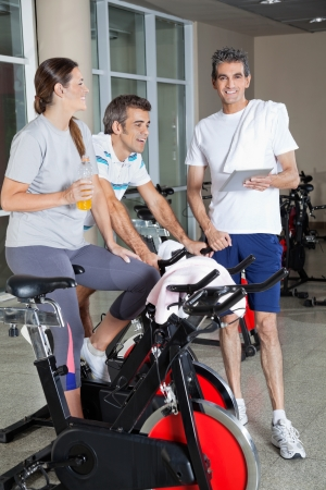 Portrait of happy man holding digital tablet while friends exercising on spinning bike in fitness club photo