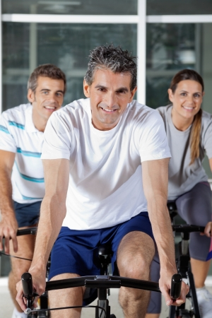 Portrait of three happy people on exercise bikes in health club photo