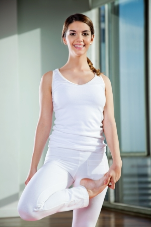 Portrait of a happy young woman practicing yoga at gym photo