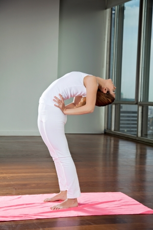 Full length of a young woman practicing yoga and making backbend at gym photo