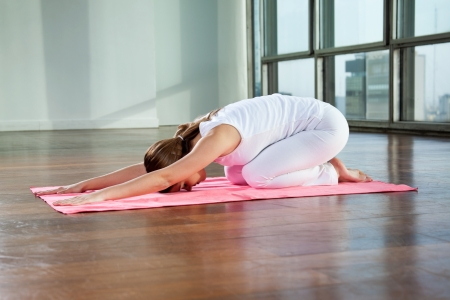 child s: Full length of a young woman sitting in child s pose on a yoga mat