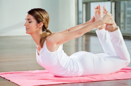 Relaxed young woman practicing yoga exercise called Bow Pose photo
