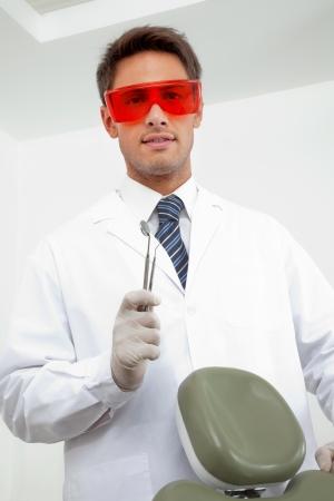 trinchante: Retrato del dentista masculino joven que llevaba gafas de protecci�n mientras se mantiene espejo en �ngulo y tallista en la cl�nica