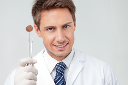 Close-up portrait of happy male dentist holding angled mirror and carver in clinic photo
