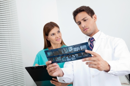Dentist with dental nurse analyzing patient s X-ray report in clinic Stock Photo - 15335785