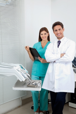 Portrait of young male dentist and assistant standing in dental clinic photo