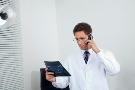 comunicacion oral: Dentista masculino joven que mira de rayos X durante el uso de teléfono celular informe en la clínica