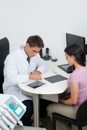 comunicacion oral: Paciente de sexo femenino con el médico de Uso de Tablet PC en el escritorio en la clínica dental