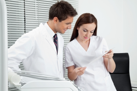 oral communication: Male dentist with assistant discussing report in clinic Stock Photo