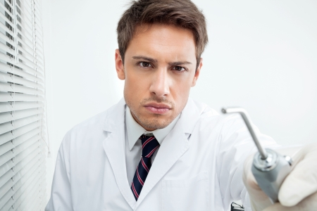 male dentist: Portrait of young male dentist holding water spraying tool