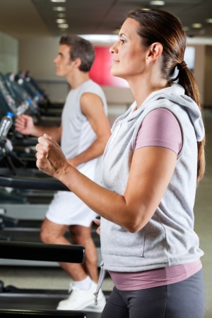 Profile shot of mature woman and man running on treadmill in health club photo