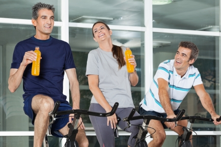 Happy young man looking at friends holding juice bottles while exercising on spinning bike in health club photo