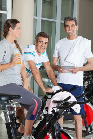 Portrait of happy male friends with woman in fitness club photo