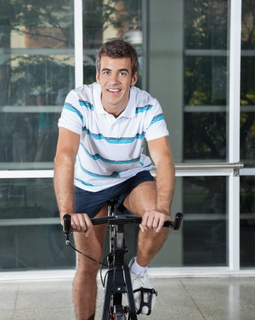 Portrait of young man exercising on spinning bike in health club photo