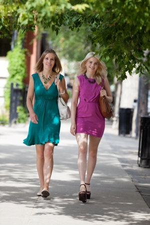 down town: Full length of pretty young women walking on sidewalk Stock Photo