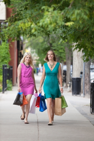 Full length of young women with shopping bags walking on sidewalk photo