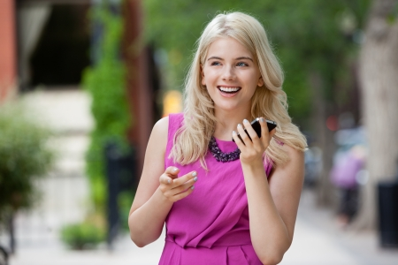 speaker phone: Happy smiling woman talking on cell phone outdoors in city Stock Photo