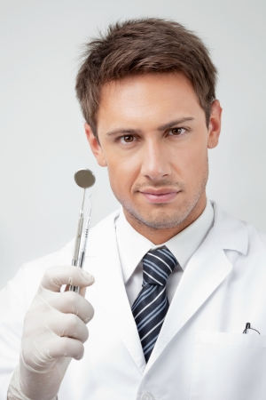 carver: Portrait of young male dentist holding angled mirror and carver in clinic