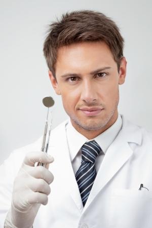 trinchante: Retrato de hombre joven con dentista espejo en �ngulo y tallista en la cl�nica