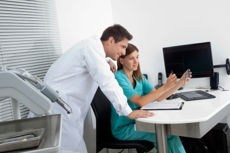 Young male dentist with assistant analyzing report in clinic Stock Photo - 15353500