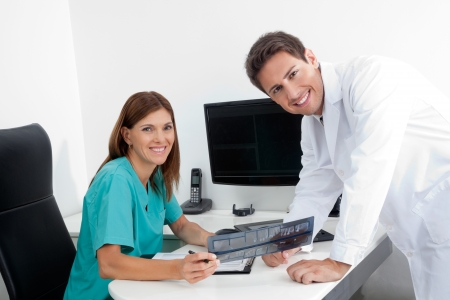 Portrait of happy dentist and female assistant analyzing X-ray report at office desk Stock Photo - 15353485