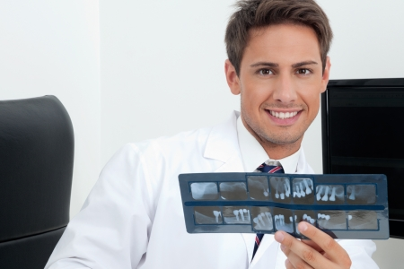 Portrait of a young handsome male dentist holding X-ray report in clinic photo