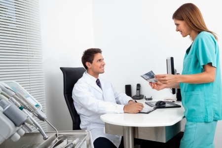 Male doctor with assistant holding X-ray report at office desk Stock Photo - 15353559