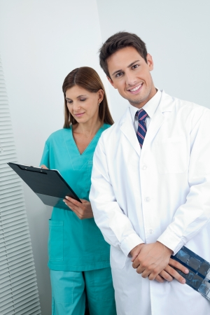 Portrait of happy male dentist with assistant holding clipboard in clinic photo