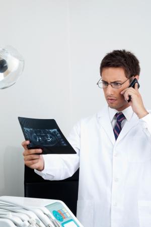comunicacion oral: Médico varón joven mirando de rayos X informe durante el uso de teléfono móvil en la clínica dental Foto de archivo