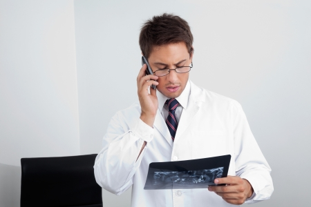 Young male dentist looking at X-ray report while using cellphone in clinic Stock Photo - 15353467