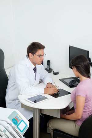 oral communication: Young male dentist showing dental X-ray report to patient in clinic Stock Photo