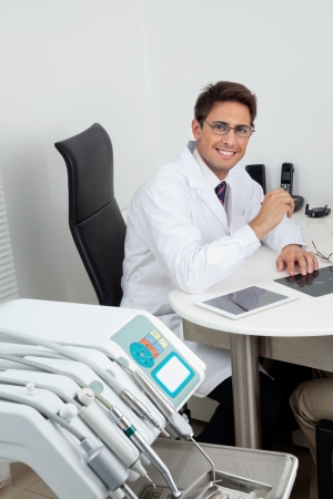 Portrait of a happy young male dentist sitting at office desk photo